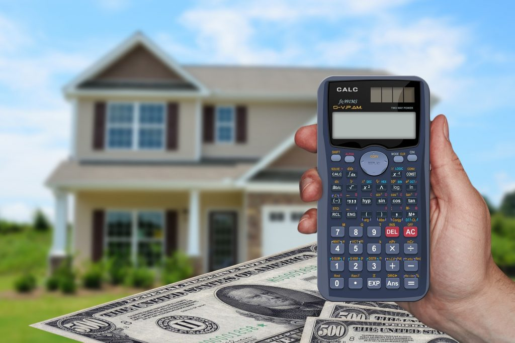 Person holding calculator with home and money in background